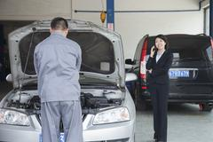 Woman Talking on Phone While Mechanic Fixes Her Car - stock photo