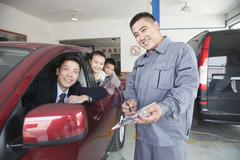 Mechanic Helping Family with Their Car - stock photo
