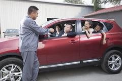 Mechanic Giving Car Keys to Family Stock Photos