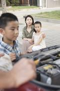 Mother and Daughter Watch as Father and Son Try to Fix the Car - stock photo