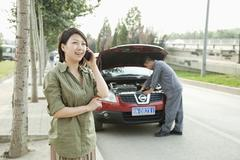 Woman Talking on Phone While Mechanic Fixes Her Car Stock Photos
