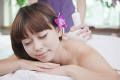 Woman Receiving Herbal Massage - stock photo