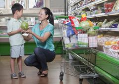 Mother and son buying watermelon in supermarket, Beijing - stock photo