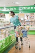 Woman shopping in supermarket, looking down in refrigerated section, Beijing - stock photo