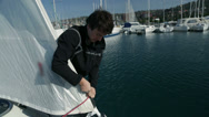 Stock Video Footage of Sailor preparing sailboat for sail in bay
