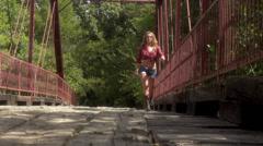 old bridge -pretty redhead country girl walking on bridge Stock Footage