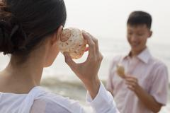 Young couple looking at seashells, holding shell to ear Stock Photos