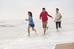Three friends running on the beach by the waters edge, China - stock photo