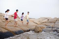 Neljä kaveria kävely yli kivien meren rannalla Kuvituskuvat