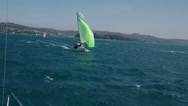 Stock Video Footage of Sailboat with green main sail on wide open sea
