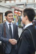 Stock Photo of Two young businessman handshaking in houhai, Beijing, China