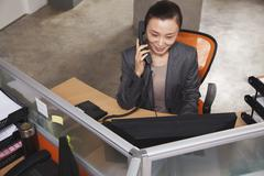 Mid adult businesswoman on the phone in the office Stock Photos