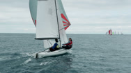 Stock Video Footage of Two man sailing on a small saiboat in open sea