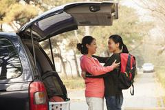 Mother and daughter embracing behind car on college campus Stock Photos