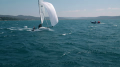 Competition sailboat with assistance in background - stock footage