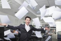 White-collar worker throwing white sheets in air in office Stock Photos