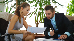 young couple business people study and discuss the schedule - stock footage