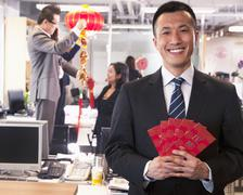 Businessman holding red envelopes and coworkers hanging decorations for Chinese - stock photo