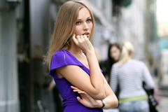 woman with a bag smiling on urban background - stock photo