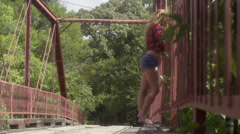 Stock Video Footage of country bridge -sexy redhead poses on old country bridge
