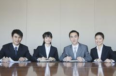 Four Young business people sitting in a row at a conference table, portrait Stock Photos