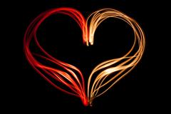 light painting heart shape over black background - stock illustration