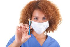 african american nurse holding a needle - black people - stock photo