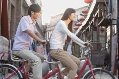 Side View of Young Heterosexual Couple on a Tandem Bicycle in Beijing - stock photo