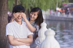 Woman Covering Mans Eyes by a Lake Stock Photos