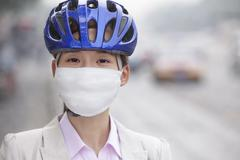 Stock Photo of Young Business Woman Wearing Bicycle Helmet and Face Mask