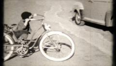 532 - young boy rides bicycle with dads help - vintage film home movie Stock Footage