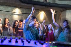 A view from DJ's deck of a crowd dancing in nightclub, - stock photo