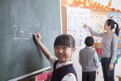 Schoolgirl doing math equation on the black board - stock photo