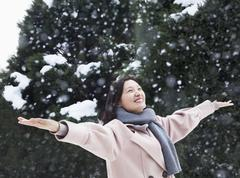 Woman with arms outstretched feeling the snow Stock Photos