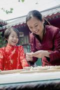 Mother and daughter making dumplings in traditional clothing - stock photo