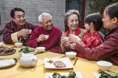 Family with cups raised toasting over a Chinese meal Kuvituskuvat