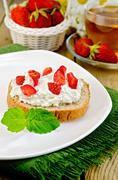 Bread with curd cream and strawberries on a board Stock Photos