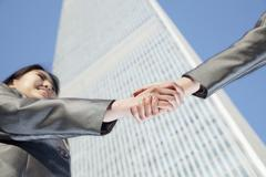 Close up of two business people shaking hands by the china world trade center in Stock Photos