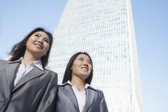 Two businesswomen standing in front of Chinas world trade center in Beijing - stock photo
