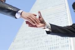 Close-up of two business people shaking hands by the World Trade Center in Stock Photos