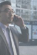 Businessman on the phone on other side of glass wall Stock Photos