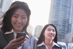 Portrait of two businesswomen, one looking at phone, outdoors Beijing - stock photo