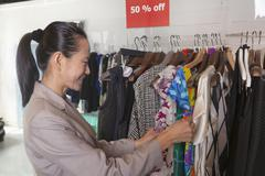 Woman going through clearance clothes at fashion store Stock Photos