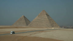 Wide shot of two pyramids and city in background Stock Footage
