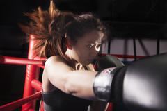Close up of female boxer throwing a punch, hair in motion Stock Photos