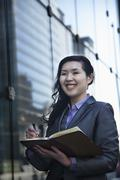 Smiling businesswoman writing in her personal organizer, outside in Beijing - stock photo