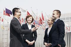 Four smiling multi-ethnic business people talking outdoors in Beijing, china - stock photo