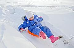 Little girl on a sled sliding on snow Stock Photos