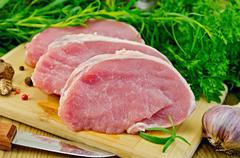 meat pork slices on a board with greens - stock photo