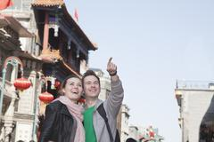 Young couple sightseeing, looking and pointing. Stock Photos